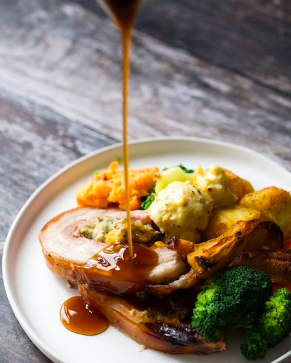 Plate with sunday dinner with gravy pouring on top